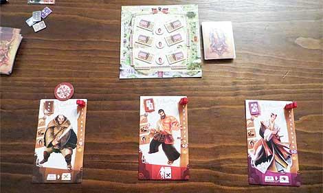 Preparación tipo para tres samuráis, con sus tableros personales y el pueblo a defender